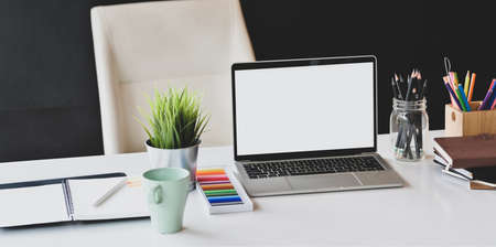 Foto de Designer workplace with open blank screen laptop and office supplies on white table and black wall background - Imagen libre de derechos