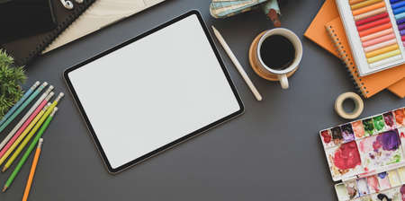 Photo pour Top view of professional artist workplace with blank screen tablet and painting tools on the grey background table - image libre de droit