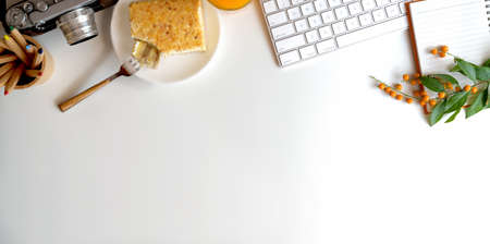 Photo pour Top view of comfortable workspace with camera and breakfast on white table with copy space - image libre de droit