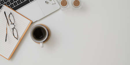 Photo for Top view of minimal workspace with laptop computer, a cup of coffee and office supplies on white desk background  - Royalty Free Image