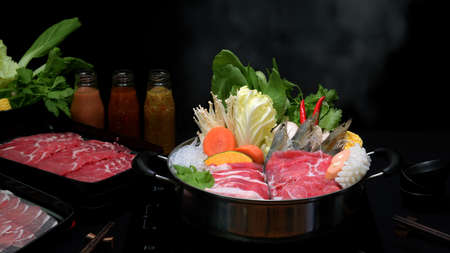Foto de Close-up view of shabu shabu in hot pot with black background, fresh sliced meat, sea food and vegetables, Japanese hotpot style - Imagen libre de derechos