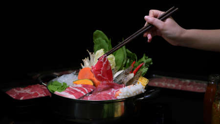 Photo pour Cropped shot of woman eating Shabu-Shabu in hot pot with fresh sliced meat, sea food, and vegetables with black background, Japanese cuisine - image libre de droit