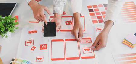 Foto de Cropped shot of young UX graphic designer team working on smartphone template together - Imagen libre de derechos