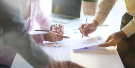 Photo pour Close-up view of young professional business team brainstorming the project with document and charts in office room - image libre de droit