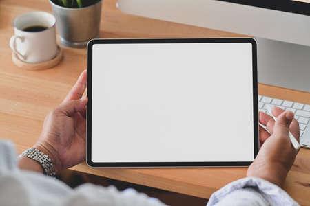 Foto de Cropped shot of young man holding blank screen digital tablet in comfortable workplace - Imagen libre de derechos