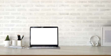 Photo for Cropped shot of modern stylish workplace with open blank screen laptop computer and office supplies on marble desk and brick wall background - Royalty Free Image