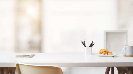 Photo for Close up view of simple workspace with copy space, frame, stationery, coffee cup and croissant on white table with blurred background - Royalty Free Image