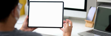 Cropped shot of male entrepreneur reading informations on blank screen tablet while sitting at workspace