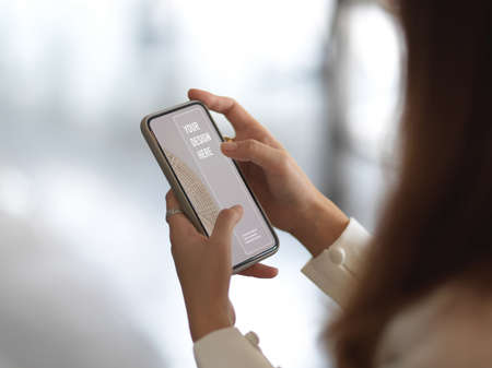 Photo pour Side view of female hands using mock up smartphone in blurred background - image libre de droit