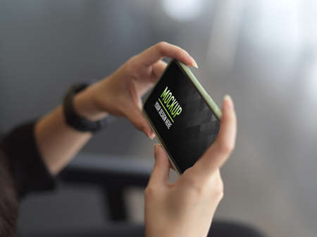 Photo pour Side view of female hands holding horizontal smartphone in blurred background - image libre de droit