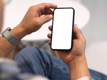 Photo for Close up view of man freelancer hands using smartphone with mock up screen in blurred background, clipping path - Royalty Free Image