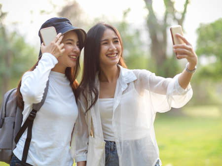 Photo pour Portraits of two young female travellers taking photo with smartphone while walking around in the park - image libre de droit