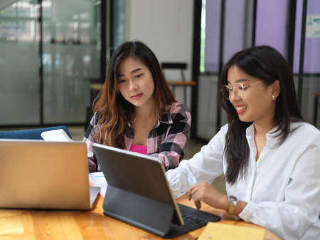 Photo for Cropped shot of two young female students consulting on their group assignment in library - Royalty Free Image