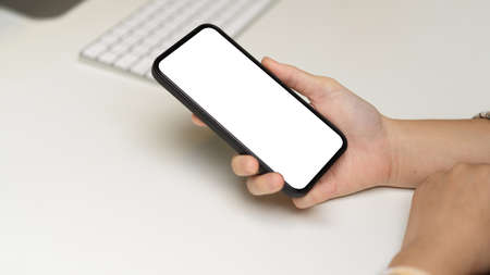 Photo pour Side view of female hand holding smartphone with mock-up screen on computer desk, clipping path - image libre de droit
