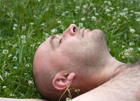 Fum man rest on green grass during summer day