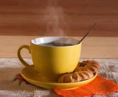 Photo pour Cup of hot tea with steam on wooden background. Light tone. - image libre de droit