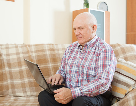 Confident middle-aged man sitting on  couch with  laptop