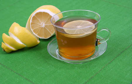 a cup of tea with lemon on green background