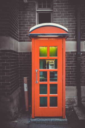 Vintage UK red phone booth in front of a brick wall