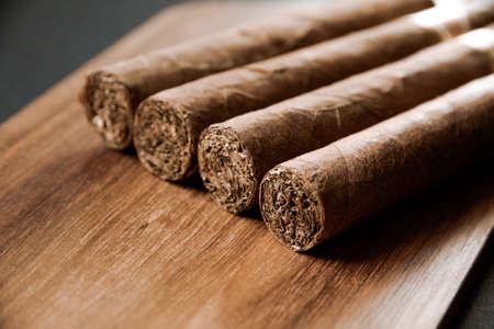 Photo pour Group of brown cuban cigars on old wooden background - image libre de droit