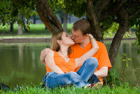 Loving couple kisses under a tree on a river bank
