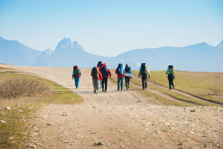 Hikers walk along the rocky footpath