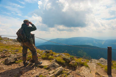 Hiker stands on a peak and enjoy the scenery through binoculars