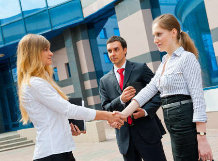 Business people shaking hands in a modern downtownの写真素材