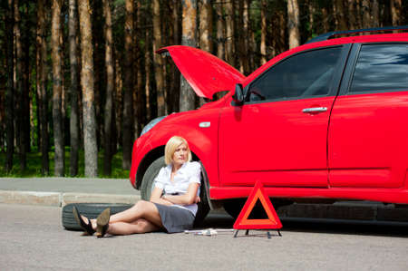 Blonde girl helplessly sitting on the road waiting for car service