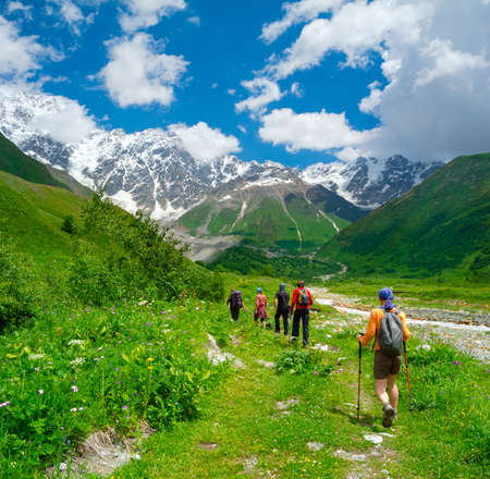 Young hikers trekking in Svaneti, Georgia. Shkhara mountain in the background