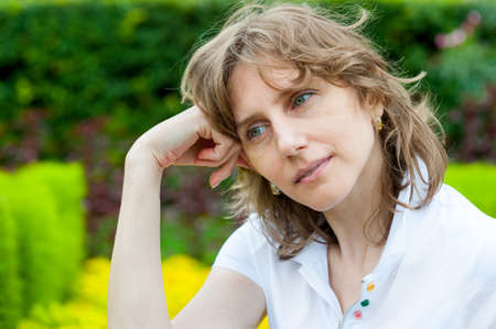 Middle age woman thinking in a park