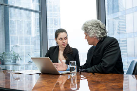 Photo pour Mature businessman and young business woman discussing in a modern office - image libre de droit