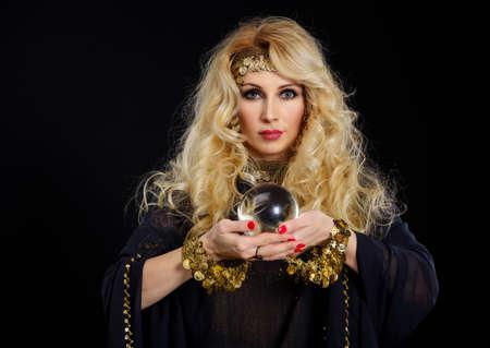 Photo pour Woman fortune teller with crystal ball portrait on black - image libre de droit