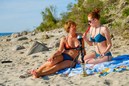 Two young girls smoking a hookah on the sandy beach