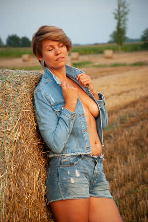 Photo pour Sexy young woman posing on the field near a haystack - image libre de droit