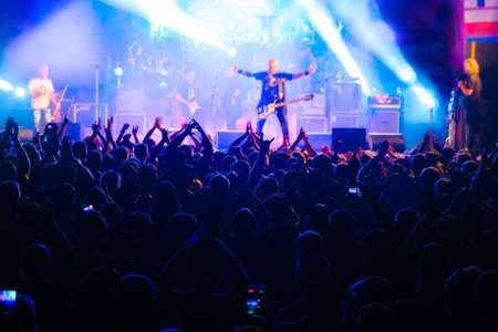 Photo pour Fans at live rock music concert cheering musicians on stage, back view - image libre de droit