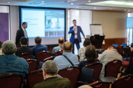 Photo pour Audience listens lecturer at workshop in conference hall, rear view - image libre de droit