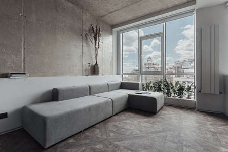 Photo pour the living room with a long grey sofa near the panoramic window, the walls are decorated as a concrete surface. Minimalist decor, room plants by the window - image libre de droit