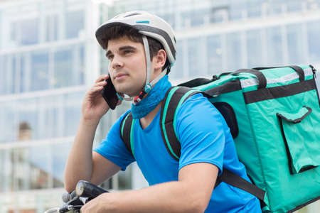 Photo pour Courier On Bicycle Delivering Food In City Using Mobile Phone - image libre de droit