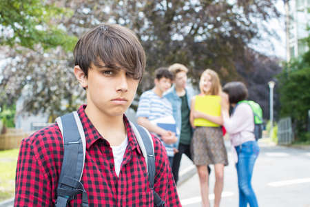 Unhappy Boy Being Gossiped About By School Friends