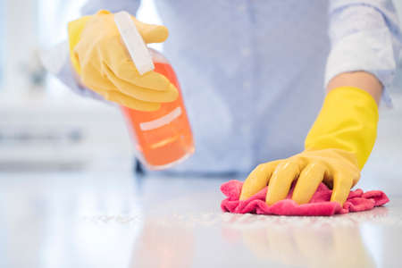 Photo for Close Up Of Woman Using Spray Polish To Clean Kitchen Surface - Royalty Free Image