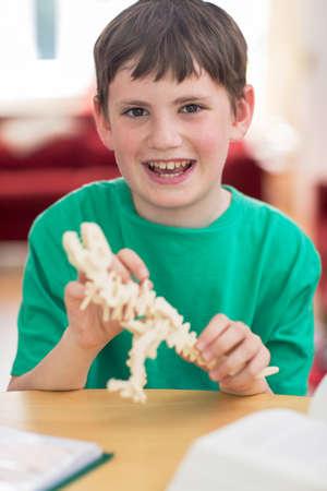 Photo pour Portrait Of Boy Making Model Dinosaur At Home - image libre de droit