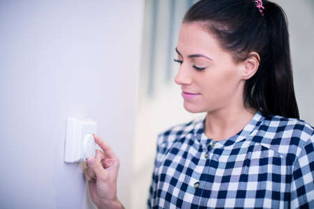 Photo for Woman At Home Adjusting Central Heating Thermostat Control - Royalty Free Image
