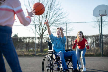 Foto de Teenage Boy In Wheelchair Playing Basketball With Friends - Imagen libre de derechos