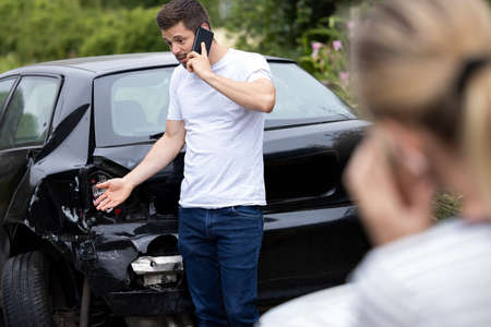 Photo pour Male Driver On Phone Call To Insurance Company After Accident With Female Motorist - image libre de droit