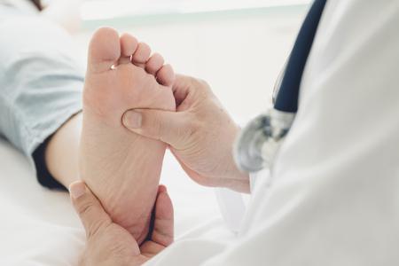 Photo pour Doctor giving a patient foot treatment - image libre de droit