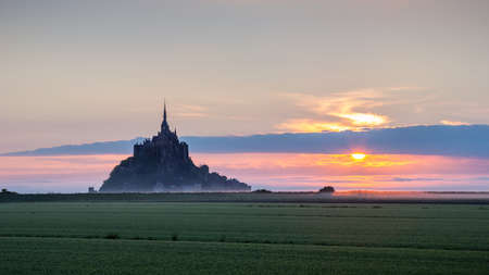Beautiful panoramic view of famous Le Mont Saint-Michel tidal island at sunrise. Normandy, northern France
