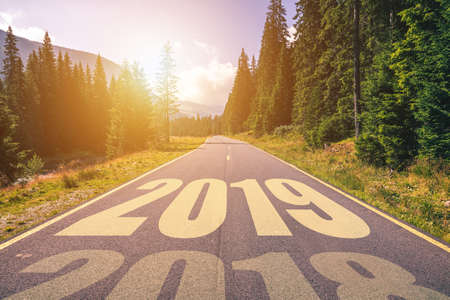 Empty asphalt road and New year 2019 concept. Driving on an empty road in the mountains to upcoming 2019 and leaving behind old 2018. Concept for success and passing time.