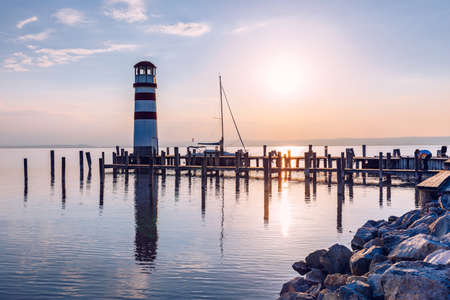 Lighthouse at Lake Neusiedl, Podersdorf am See, Burgenland, Austria. Lighthouse at sunset in Austria. Wooden pier with lighthouse in Podersdorf on lake Neusiedl in Austria.