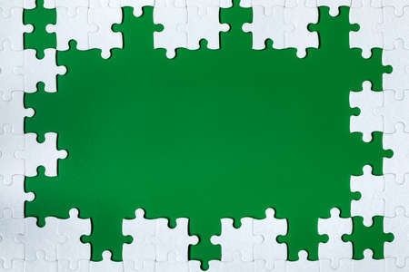 Framing in the form of a rectangle, made of a white jigsaw puzzle. Frame text and jigsaw puzzles. Frame made of jigsaw puzzle pieces on green background.